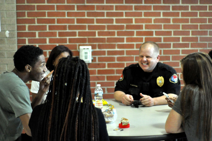SRO+Rob+Woyicki+interacts+with+senior+Isaiah+Jones+%28left%29+and+other+students+during+a+lunch+period+March+28.+One+of+the+benefits+of+having+a+school+resource+officer+has+been+cited+in+creating+a+positive+relationship+between+students+and+police.+