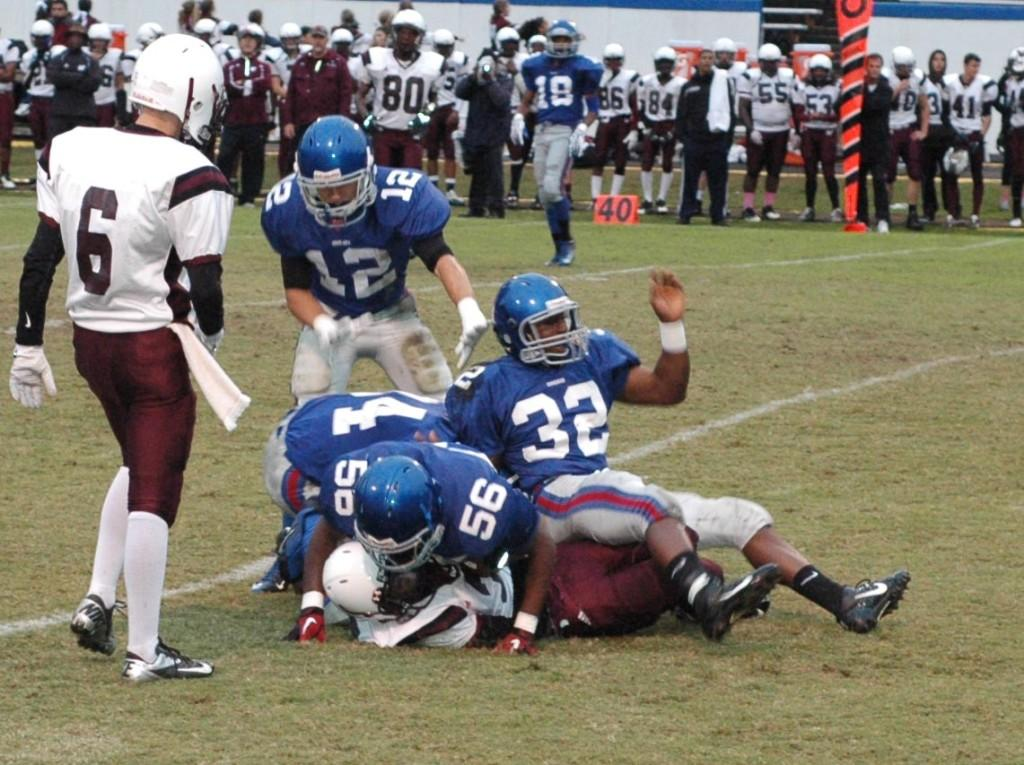 Sophomore linebacker Brandon Medlin, #32, and sophomore defensive lineman Eric Williamston, #56, swarm a Wolverine ball carrier in the 48-14 rout.