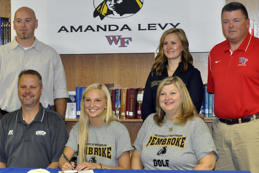 Senior+Amanda+Levy+sits+with+her+parents+as+she+signs+her+commitment+to+UNC+Pembroke.+Also+with+Levy+are+her+coach+Kevin+Lynch+%28left%29+and+athletic+direct+Mike+Joyner+%28right%29.+