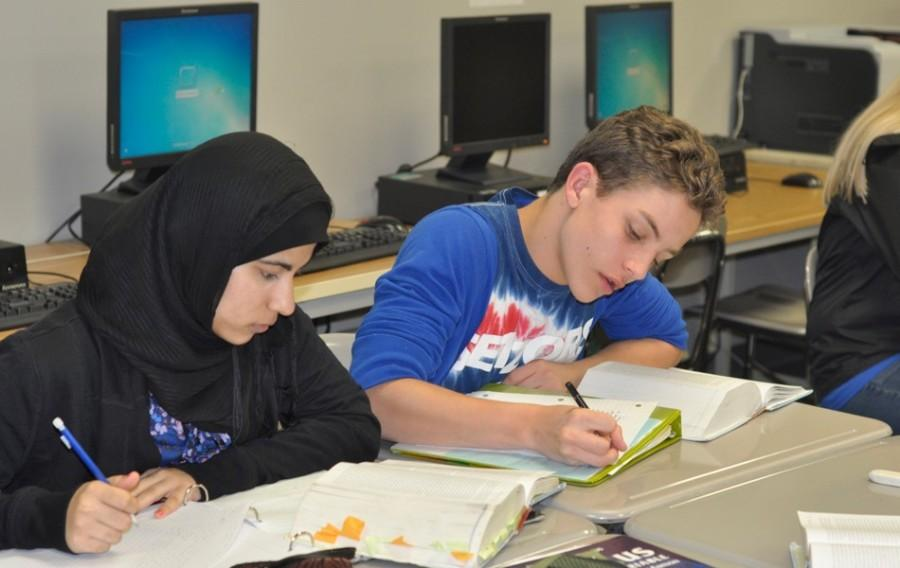 Senior AP English students Aisha Hassan and Danny Bottinelli complete an analysis of a short story. Fees for the AP Literature test will be paid for by the state should the students opt to take the test.