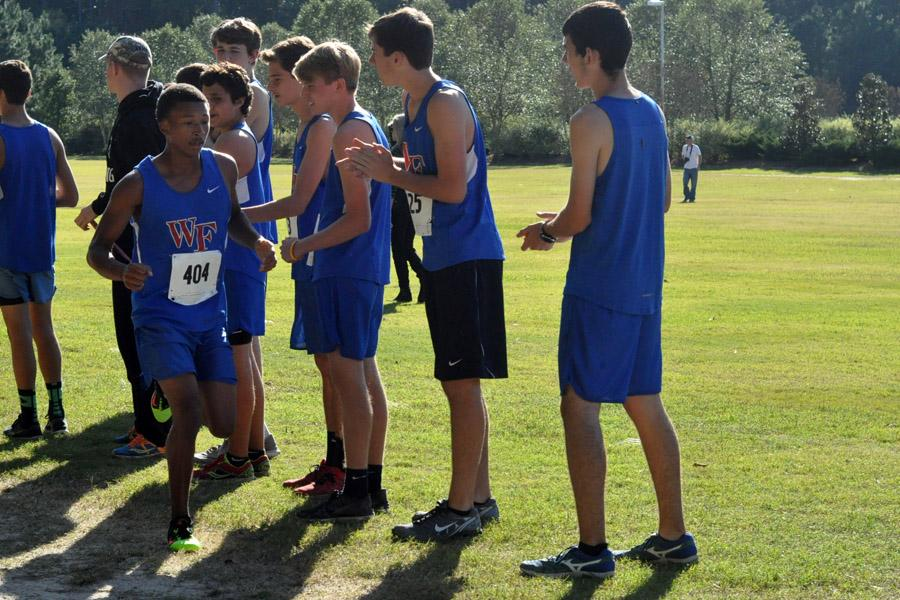 Senior Trelek Jones, who placed 1st for the Cougars at the Cap-8 conference meet, is cheered on by JV teammates in the closing stretch of the race.