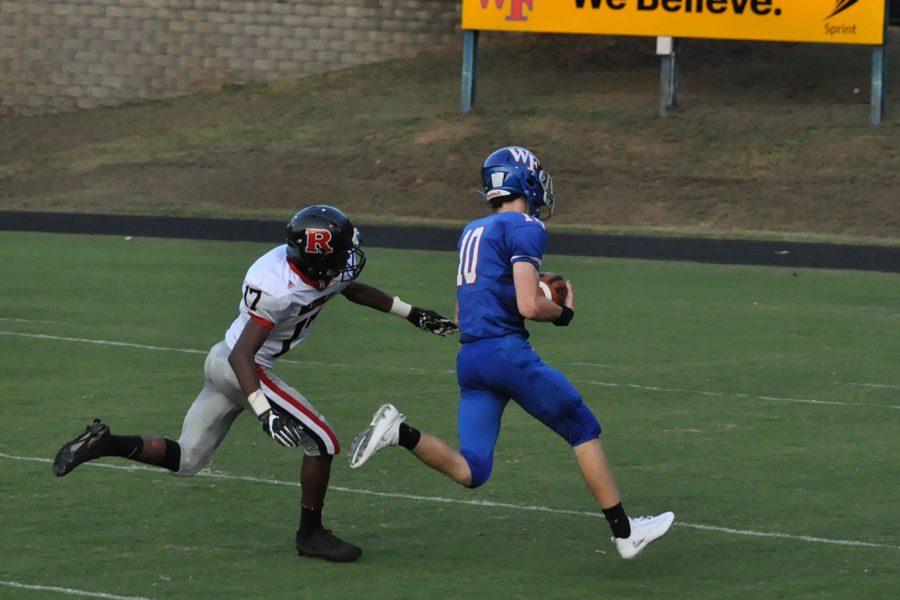 Senior receiver Gunnar Carrigan attempts to gain yards against Rolesville.