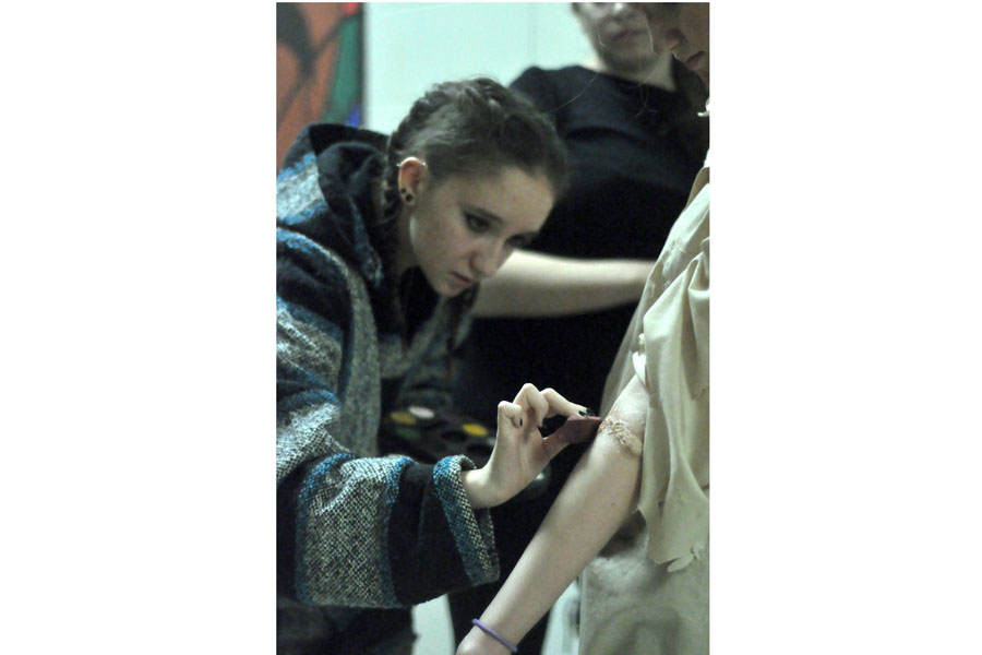 Senior Erin Morales works on a cast member in the production of