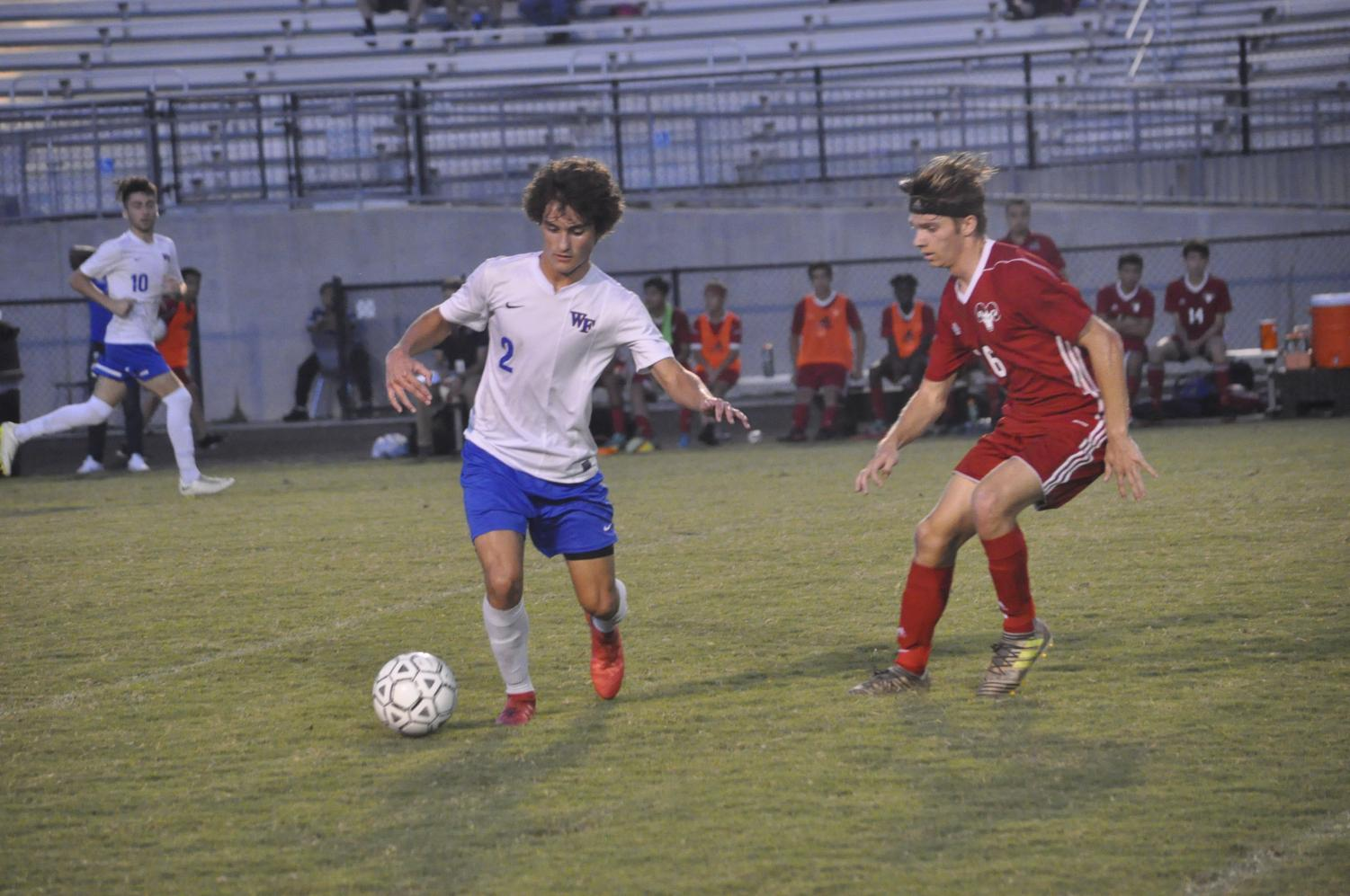 Sophomore Chris Steg carries the ball up the field in a conference match against Rolesville. Steg was the leading goal scorer for the Cougars, seeing the back of the net 25 times this season.