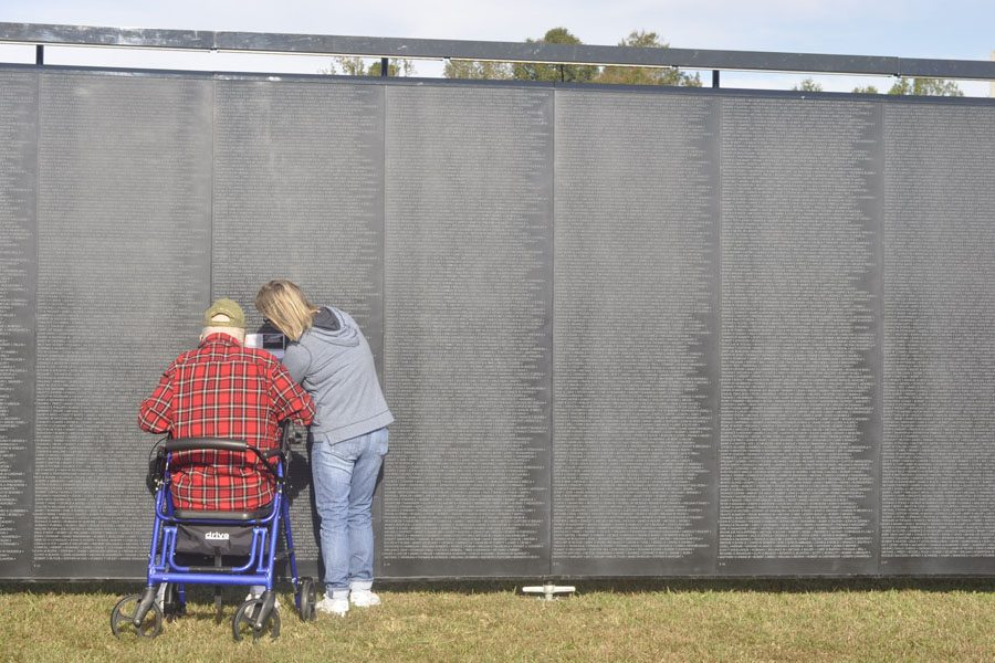 John Dermott etches the name of a fallen soldier with the help of a family member. Dermott visited the memorial to pay respects to all of the veterans who risked their lives so we could live ours.
