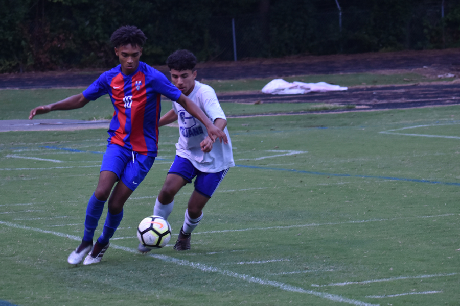 Senior mid-fielder Chris Guccio works against his Garner defender in a match the Cougars won 4 to 0.